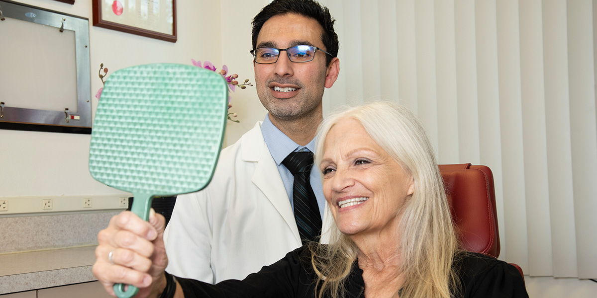Patient smiling looking at new implant-supported teeth