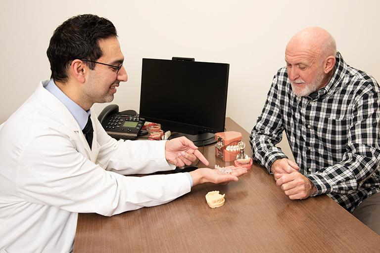 Dentist showing patient dental implant